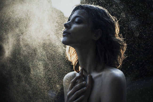 Eine Frau badet in Wasserstaub.
