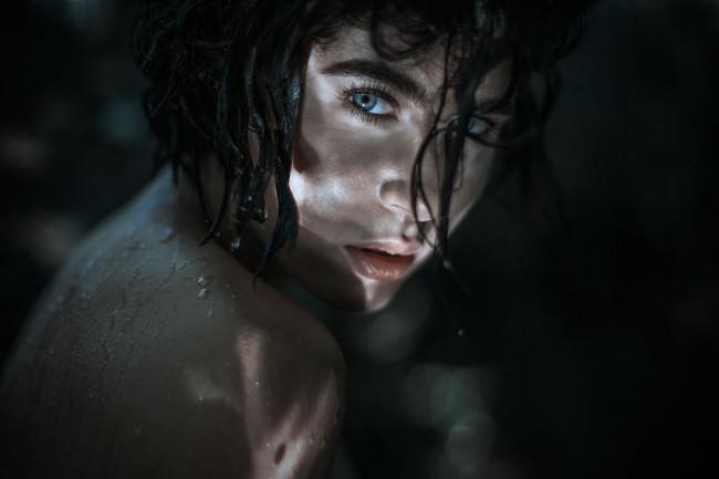Eine Frau mit Wasserreflexen im Gesicht.
