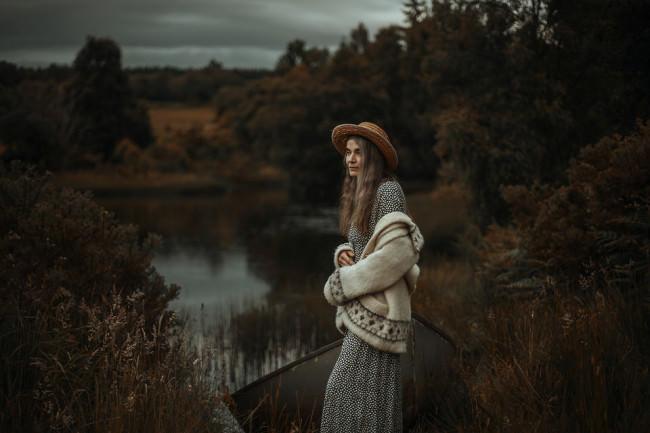 Eine Frau steht an einem See.