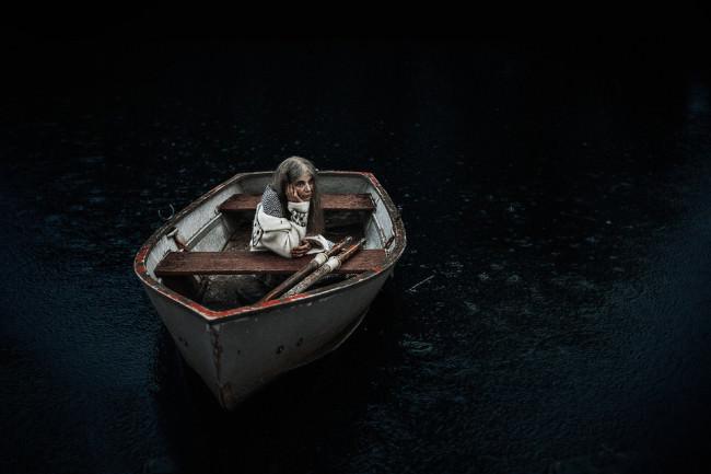 Eine Frau sitzt wartend in einem Ruderboot.