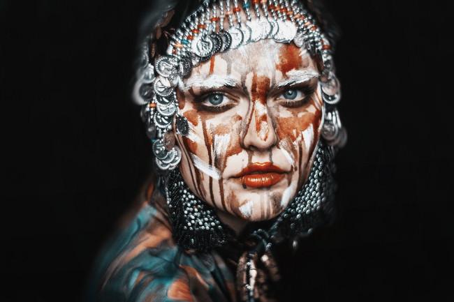 Eine Frau mit Farbe uns Schmuck im Gesicht.