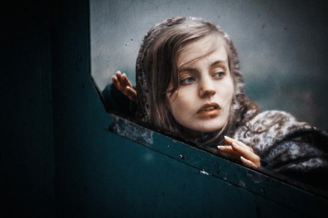 Eine Frau sieht durch ein Fenster