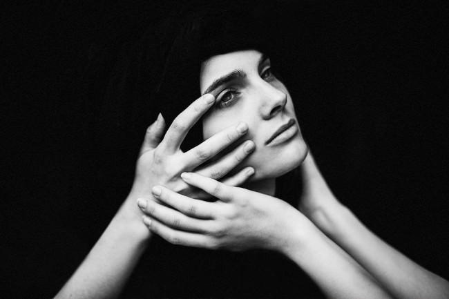 Eine Frau, deren Kopf von drei Händen gehalten wird.