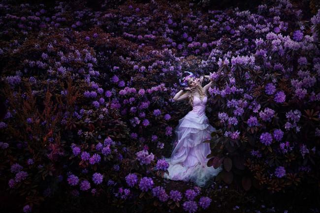 Eine Frau mit Hörnern und weißem Kleid in einem Fliederbusch