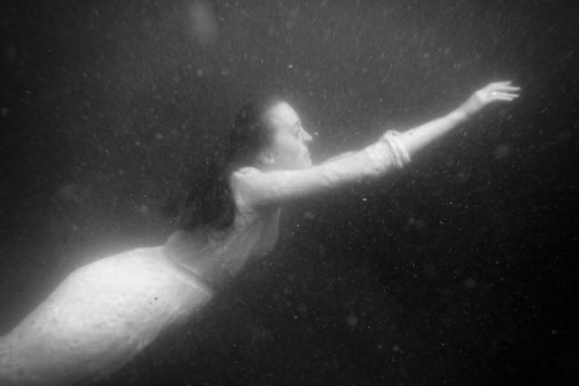 Eine Frau schwimmt Unterwasser.