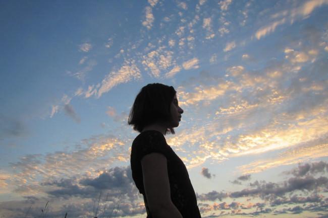 Eine Frau vor einem Wolkenhimmel.