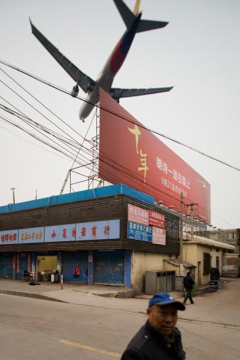 landendes Flugzeug über einem Gewerbebetrieb