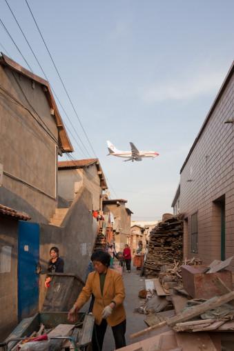 landendes Flugzeug über einer geschäftigen Gasse