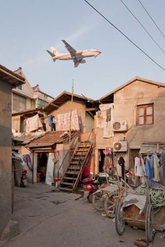 tieffliegendes Flugzeug über einem kleinteiligen Wohngebiet