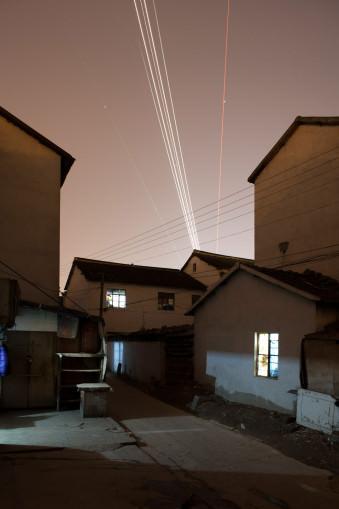Langzeitbelichtung eines startenden Flugzeugs über einer dunklen Gasse