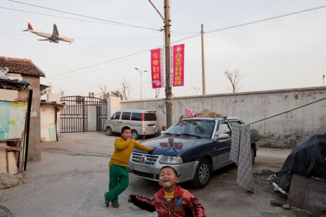 spielende Kinder auf einer Straße in der Nähe eines Flughafens