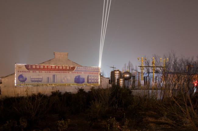 Langzeitbelichtung eines startenden Flugzeugs über einem Gewerbegebiet