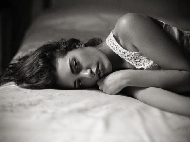 Eine Frau liegt auf dem Bett.