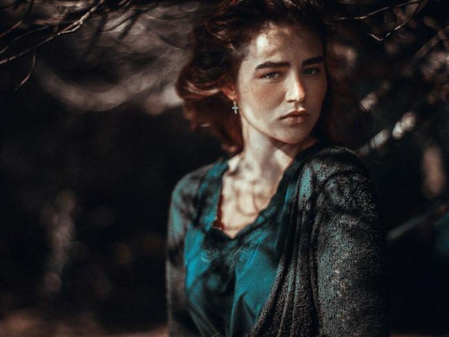 Eine Frauenportrait mit Schatten von Blättern im Gesicht.