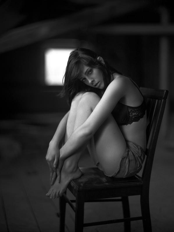 Eine Frau in Unterwäsche sitzt auf einem Stuhl.