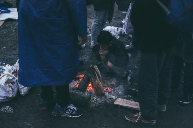 Ein Kind wärmt sich am Feuer
