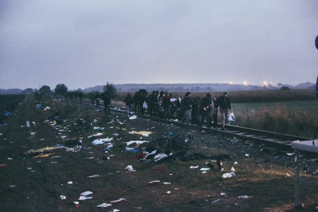 Flüchtlinge laufen auf Gleisen