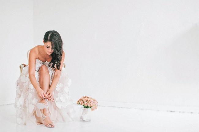 Eine Braut bindet sich die Schuhe.