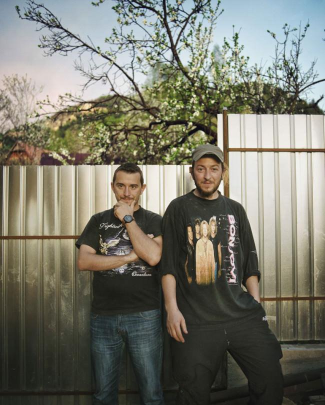 Zwei Männer stehen vor einer Wand und schauen in die Kamera.