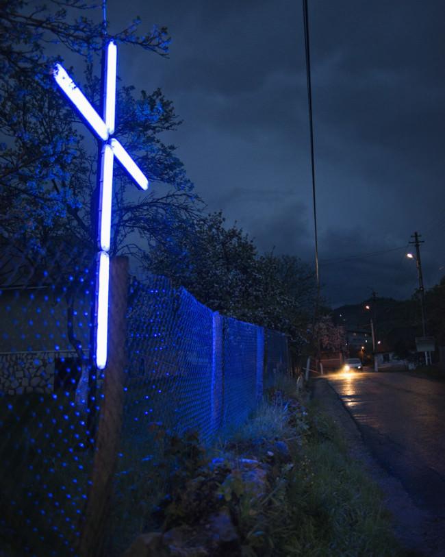 Ein Neokreuz an der Straße leuchtet vor sich hin.