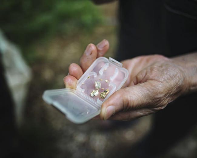 In einer Hand ein kleines Döschen mit Blick auf kleine Goldnuggets.