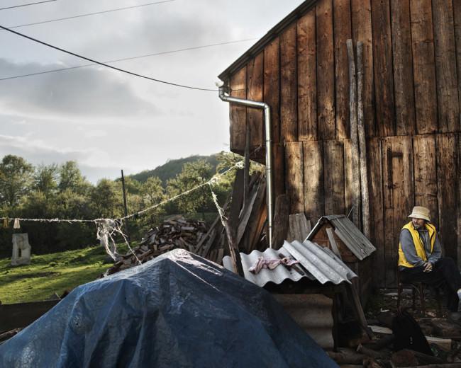 Ein Mann sitzt vor einer Hütte und blickt zur Seite.