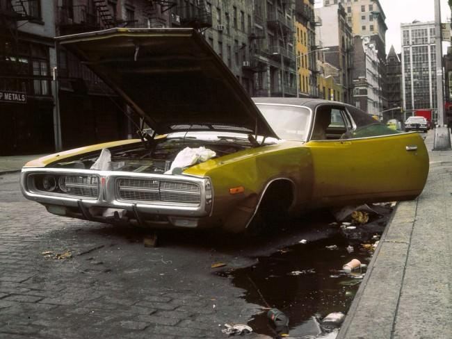 Ein kaputtes gelbgrünes Auto steht offen auf der Straße, auf ihm und ringsherum Müll.