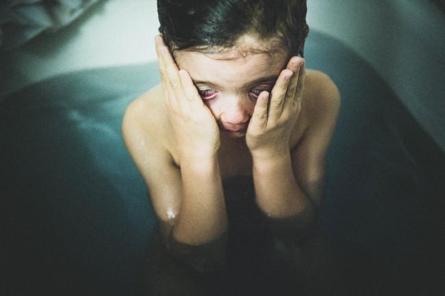 Ein Junge reibt sich die Augen in der Badewanne.