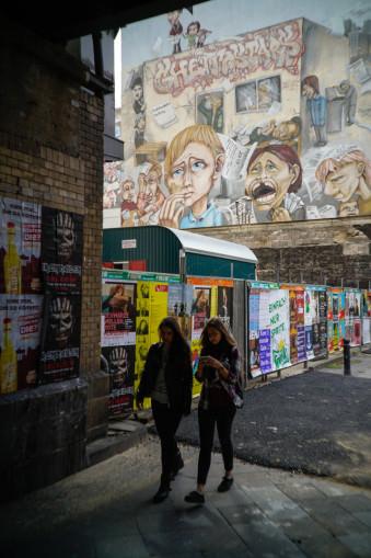 Zwei Personen laufen vor einer bemalten Wand