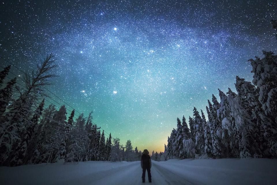 Ein Mann auf einer verschneiten Straße im Wald.