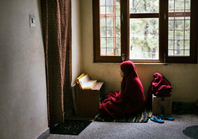 Eine Frau in roter Robe liest.