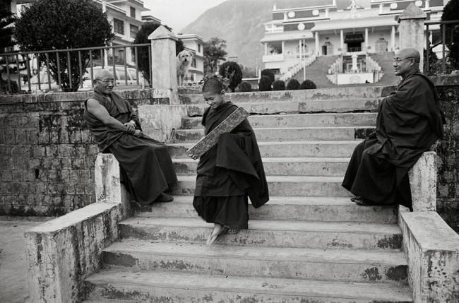 Ein Junge und zwei Mönche auf einer Treppe.