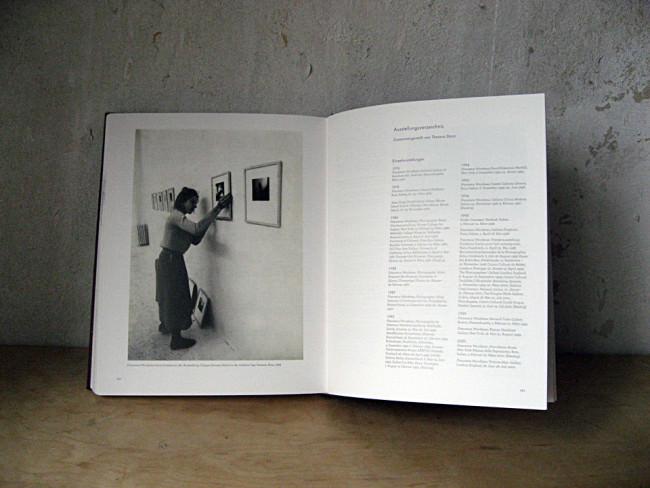 Eine Frau hängt Bilder an eine Wand.