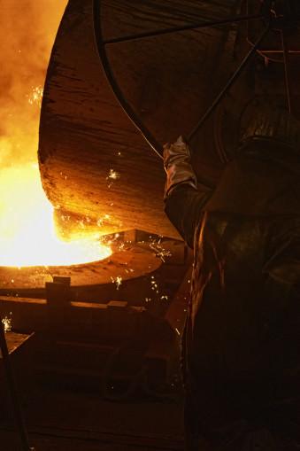 Ein Mann hält einen großen Topf, aus dem heißer, flüssiger Stahl läuft.