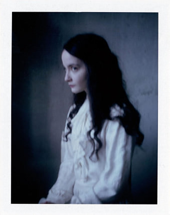 Eine Frau sitzt im Profil in einem weißen Kleid.