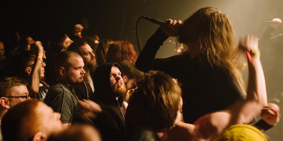 Ein Mann hält sich ein Mikrofon vor den Mund und steht in einer Menge von Menschen.