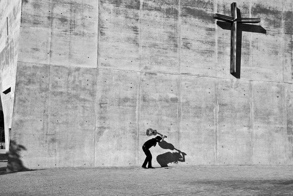 Ein Mann ist dabei, eine Gitarre auf den Boden vor einer Betonwand mit einem großen Kreuz zu schlagen.
