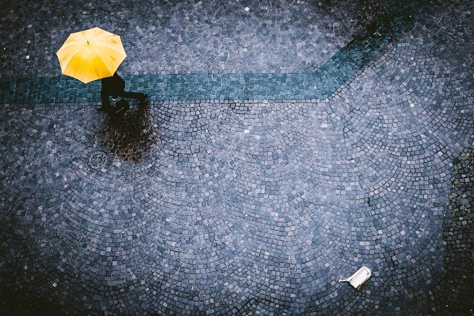 Mensch mit einem gelben Regenschirm auf Kopfsteinpflaster und etwas Weggeworfenes.