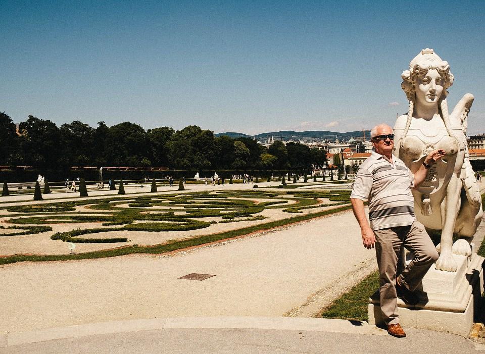 Ein Mann posiert mit Sonnenbrille vor einer Statue, seine Hand an die Brust selbiger gelegt, vor einem Schlossgarten.
