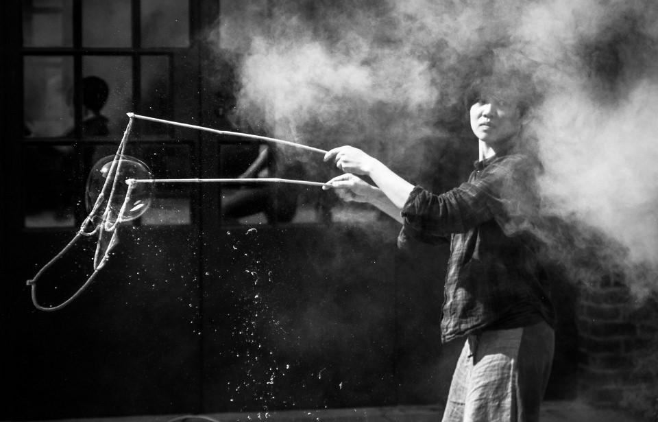 Eine Frau macht Seifenblasen mit einem Seil an Stöcken, sie steht in einer Nebelwolke und wird vom Sonnenlicht beschienen.
