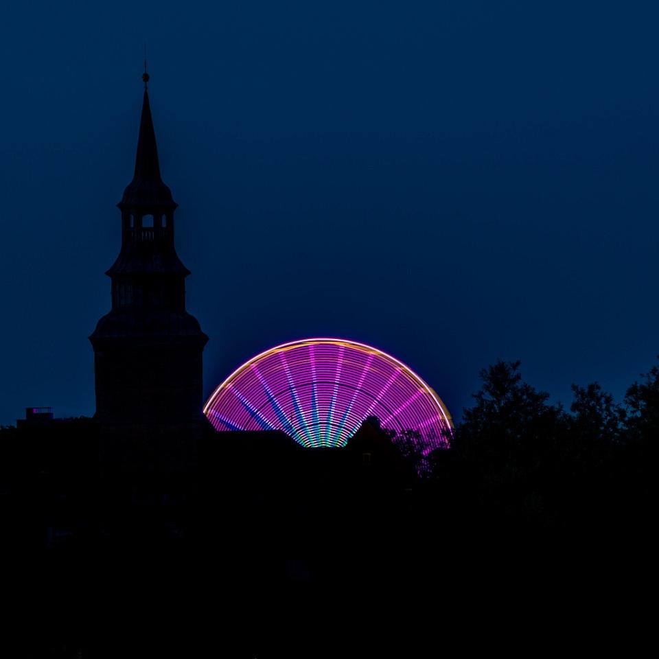Bundes, leuchtendes Halbrund eines Riesenrades vor der Silhouette einer Stadt mit Kirchturm, vor einem nachtblauen, sternenlosen Himmel.