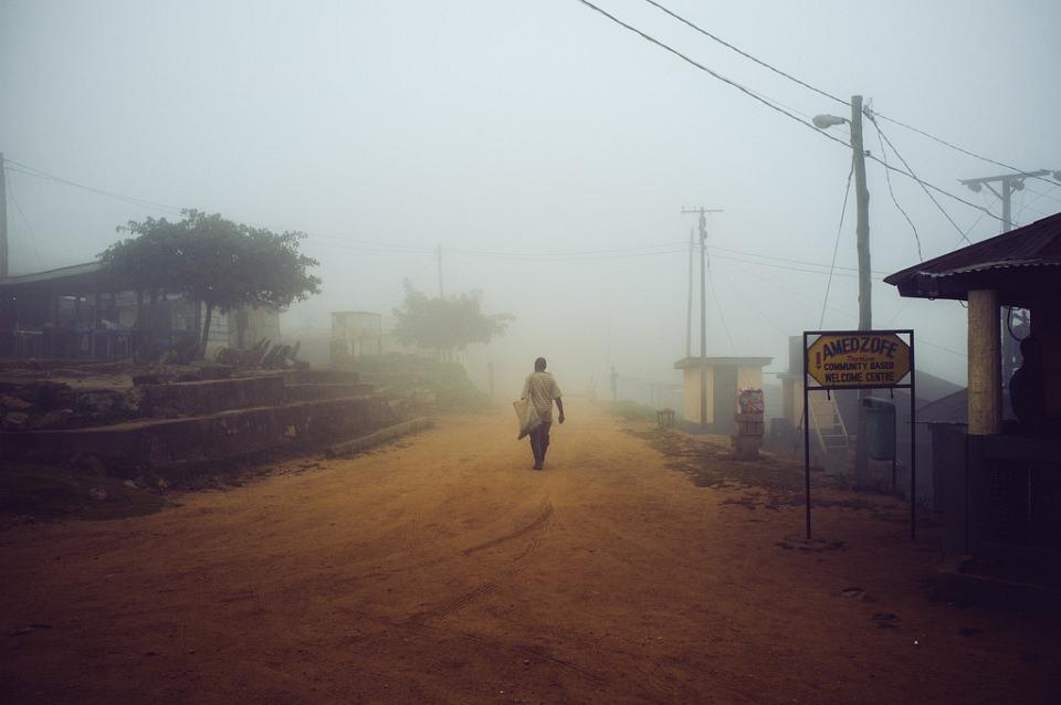 Ein Mann geht auf einer nebligen, roten Sandstraße durch ein Dorf.