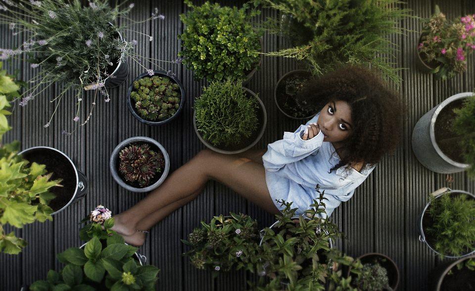 Eine Frau liegt zwischen Pflanzenkübeln auf einer Terrasse.