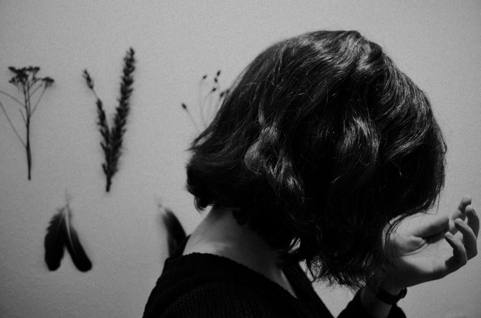 Ein Frauenkopf seitlich vor einer Wand, an der getrocknete Pflanzen hängen.