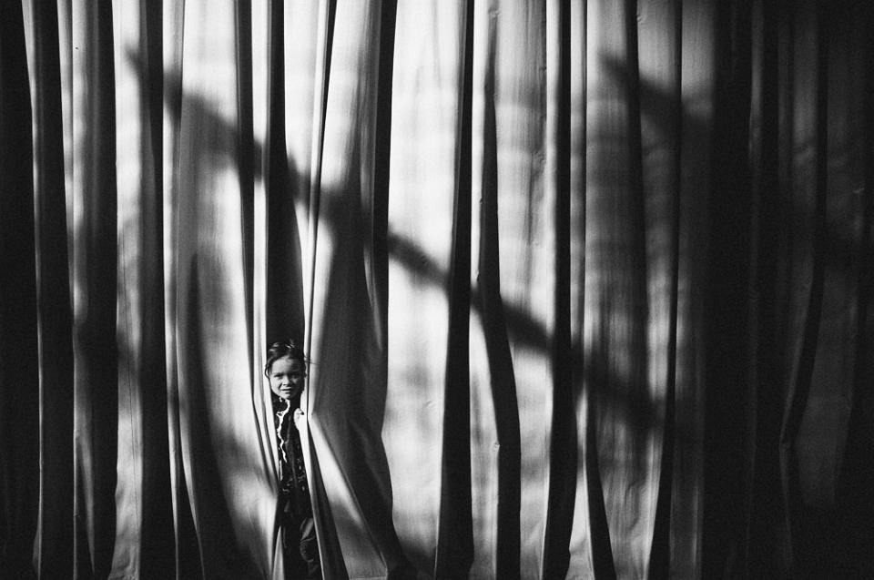 Ein Kind schaut einem sehr großen Vorhang heraus, auf dem Licht und Schatten spielen.