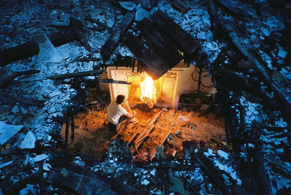 Ein Mann sitzt vor einem Kaminfeuer, betrachtet durch ein Loch in der Decke, bedeckt von Schnee und herumliegenden Holzbrettern, teilweise in den Raum darunter gefallen.