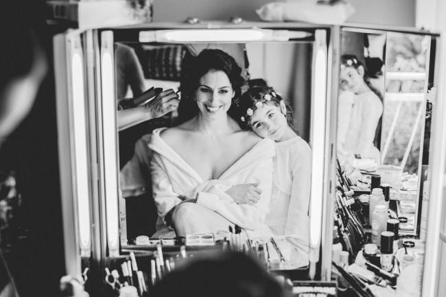 Eine Braut sitzt vor einem Spiegel. Ein Kind lehnt sich an sie.