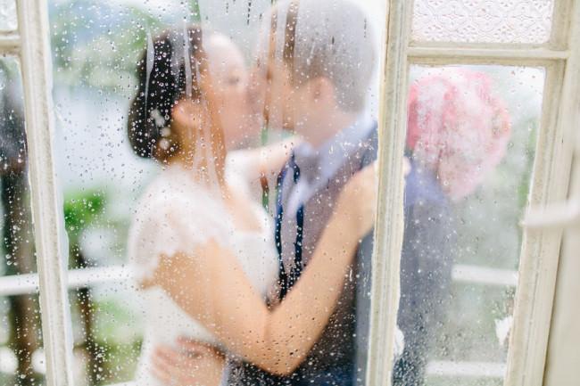 Ein Hochzeitspaar hinter einer Scheibe küsst sich