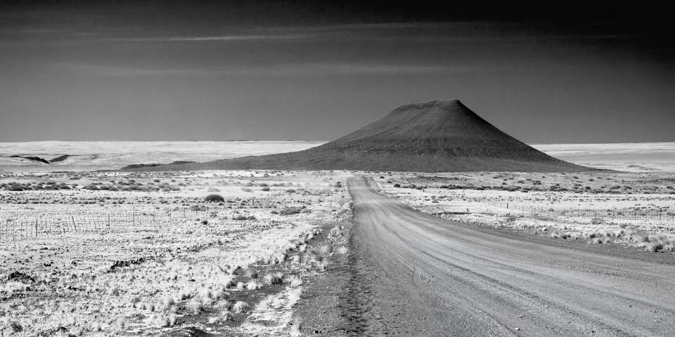 Straße durch eine Steppenlandschaft, die auf einen Berg am Horizont zuführt.