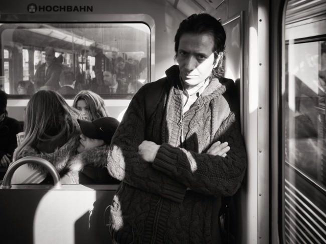 Ein Mann in Pullover steht mit verschränkten Armen in einer Hochbahn an den Türrahmen gelehnt, hinter ihm weitere Passagiere.